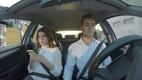Ο οδηγός και η φίλη χρησιμοποιούν τα έξυπνα τηλέφωνα και οδηγώντας και μην δίνοντας προσοχή στο δρόμο - απόθεμα βίντεο