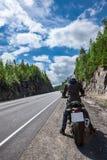Ο οδηγός μοτοσικλετών είναι έτοιμος να αρχίσει στο δρόμο ασφάλτου, καθμένος στη μοτοσικλέτα, οπισθοσκόπο Στοκ Φωτογραφία