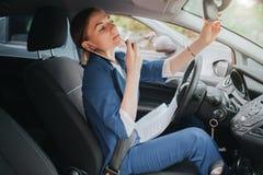 Ο οδηγός που πηγαίνει στο δρόμο, που μιλά στο τηλέφωνο, που εργάζεται με τα έγγραφα και που κάνει έναν τύπο επάνω συγχρόνως Στοκ Εικόνες