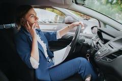 Ο οδηγός που πηγαίνει στο δρόμο, μιλώντας στο τηλέφωνο, που λειτουργεί με τα έγγραφα συγχρόνως Να κάνει επιχειρηματιών Στοκ εικόνες με δικαίωμα ελεύθερης χρήσης