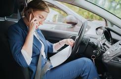 Ο οδηγός που πηγαίνει στο δρόμο, μιλώντας στο τηλέφωνο, που λειτουργεί με τα έγγραφα συγχρόνως Να κάνει επιχειρηματιών Στοκ Φωτογραφίες