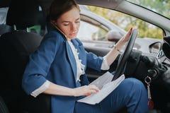 Ο οδηγός που πηγαίνει στο δρόμο, μιλώντας στο τηλέφωνο, που λειτουργεί με τα έγγραφα συγχρόνως Να κάνει επιχειρηματιών Στοκ Φωτογραφία