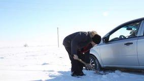 Ο οδηγός σκάβει έξω το αυτοκίνητο με ένα φτυάρι από το χιόνι φιλμ μικρού μήκους