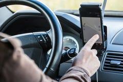 Ο οδηγός στο αυτοκίνητο ελέγχει τον πλοηγό Στοκ Φωτογραφίες