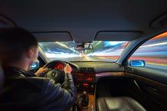 Ο οδηγός στο αυτοκίνητο κινείται με τη γρήγορη ταχύτητα τη νύχτα Στοκ Εικόνες