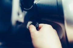 Ο οδηγός του ατόμου παίρνει ένα αυτοκίνητο με ένα κλειδί Το χέρι παρεμβάλλει το κλειδί στην ανάφλεξη και αρχίζει το αυτοκίνητο Το στοκ εικόνα