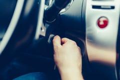 Ο οδηγός του ατόμου παίρνει ένα αυτοκίνητο με ένα κλειδί Το χέρι παρεμβάλλει το κλειδί στην ανάφλεξη και αρχίζει το αυτοκίνητο Το στοκ εικόνες
