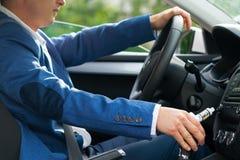 Ο οδηγός του αυτοκινήτου κάθεται πίσω από τη ρόδα και κρατά στο χέρι του ένα ηλεκτρονικό τσιγάρο στοκ εικόνα