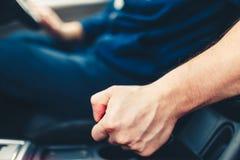 Ο οδηγός τραβά το μοχλό φρένων χεριών Αρσενικό χέρι που τραβά το φρένο χώρων στάθμευσης που χρησιμοποιεί το μοχλό φρένων χεριών Φ στοκ φωτογραφία με δικαίωμα ελεύθερης χρήσης
