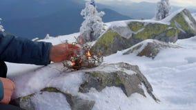 Ο οδοιπόρος αρχίζει την πυρκαγιά στα χιονώδη βουνά απόθεμα βίντεο