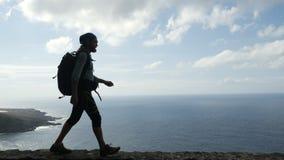 Ο οδοιπόρος ατόμων με το σακίδιο πλάτης περπατά στην άκρη ενός δρόμου στα Κανάρια νησιά επάνω από τον ωκεανό tenerife απόθεμα βίντεο