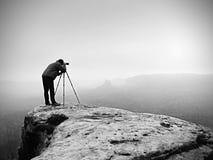 Ο οδοιπόρος με τη κάμερα στο τρίποδο παίρνει την εικόνα από τη δύσκολη σύνοδο κορυφής Μόνος φωτογράφος στη σύνοδο κορυφής Στοκ φωτογραφίες με δικαίωμα ελεύθερης χρήσης