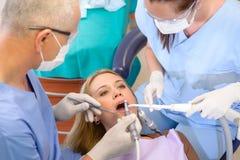 ο οδοντίατρος έχει τη γυναίκα επεξεργασίας χειρουργικών επεμβάσεων Στοκ Φωτογραφίες