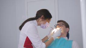 Ο οδοντίατρος ανοίγει το λαμπτήρα και κατευθύνει το φως στη συνεδρίαση ατόμων στην οδοντική καρέκλα απόθεμα βίντεο