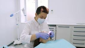 Ο οδοντίατρος βάζει το στοματικό αποσυμπιεστή για ένα όμορφο κορίτσι στο οδοντικό γραφείο απόθεμα βίντεο