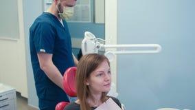 Ο οδοντίατρος γιατρών ατόμων προετοιμάζει τα υπομονετικά δόντια που λευκαίνουν στο οδοντικό γραφείο φιλμ μικρού μήκους