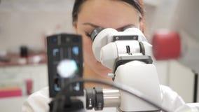 Ο οδοντίατρος γιατρών γυναικών χρησιμοποιεί ένα μικροσκόπιο Ιατρική, υγεία, έννοια στοματολογίας ο οδοντίατρος διευθύνει την επιθ φιλμ μικρού μήκους