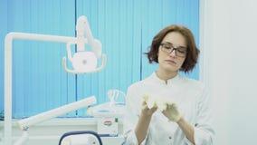 Ο οδοντίατρος γυναικών βάζει στα γάντια στο οδοντικό γραφείο μέσα Ο οδοντίατρος γυναικών σε ομοιόμορφο βάζει στα γάντια πλύσης πρ απόθεμα βίντεο