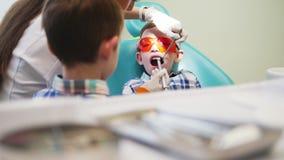Ο οδοντίατρος γυναικών οδηγεί ένα εργαλείο στο στόμα ενός υπομονετικού αγοριού Ο αδελφός αγοριών ` s στέκεται εδώ κοντά φιλμ μικρού μήκους