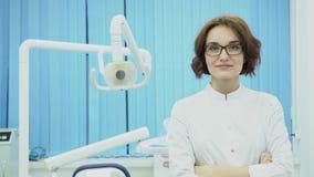 Ο οδοντίατρος γυναικών συναντά το χαμόγελο πελατών μέσα Ο οδοντίατρος γυναικών στο άσπρο παλτό καλωσορίζει το νέο πελάτη στο οδον φιλμ μικρού μήκους