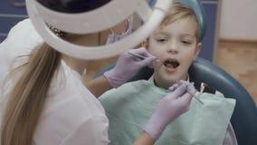Ο οδοντίατρος ελέγχει τα δόντια του μικρού παιδιού με το γωνιακούς έλεγχο και τον καθρέφτη απόθεμα βίντεο