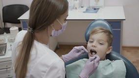 Ο οδοντίατρος ελέγχει τον όρο των δοντιών του μικρού παιδιού με το γωνιακούς έλεγχο και τον καθρέφτη φιλμ μικρού μήκους