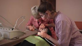 Ο οδοντίατρος εξετάζει και θεραπεύει τα δόντια απόθεμα βίντεο