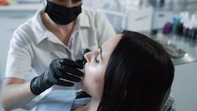 Ο οδοντίατρος εξετάζει τα υπομονετικά δόντια με τα οδοντικά εργαλεία, σε αργή κίνηση Γυναίκα στο γραφείο οδοντιάτρων απόθεμα βίντεο