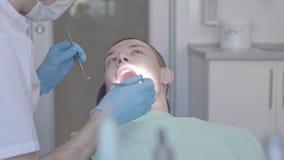 Ο οδοντίατρος εξετάζει τη στοματική κοιλότητα του ασθενή απόθεμα βίντεο