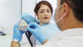 Ο οδοντίατρος εξηγεί τη διαδικασία του οδοντικού προτύπου Εβραίου εκμετάλλευσης προσθετικής στα χέρια απόθεμα βίντεο