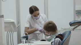 Ο οδοντίατρος επιδεικνύει πώς να καθαρίσει τα δόντια σε μια μικρή συνεδρίαση αγοριών στην καρέκλα στοματολογίας φιλμ μικρού μήκους