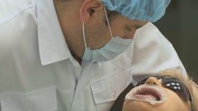 Ο οδοντίατρος θεραπεύει τον ασθενή στο σύγχρονο οδοντικό γραφείο Εργασίες Orthodontist με έναν βοηθό Σε λειτουργία, ο εγκιβωτισμό φιλμ μικρού μήκους