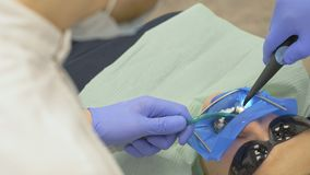 Ο οδοντίατρος θεραπεύει τον ασθενή στο σύγχρονο οδοντικό γραφείο Εργασίες Orthodontist με έναν βοηθό Σε λειτουργία, ο εγκιβωτισμό απόθεμα βίντεο