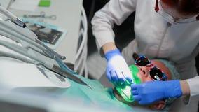 Ο οδοντίατρος και η νοσοκόμα που επισκευάζουν ένα δόντι ενός υπομονετικού ατόμου Η χρήση του bormashenko για να τρυπήσει τα δόντι απόθεμα βίντεο
