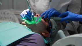 Ο οδοντίατρος και η νοσοκόμα που επισκευάζουν ένα δόντι ενός υπομονετικού ατόμου Η χρήση του bormashenko για να τρυπήσει τα δόντι φιλμ μικρού μήκους