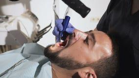 Ο οδοντίατρος μεταχειρίζεται τα υπομονετικά δόντια ` s Ιατρικά stomatological όργανα στα χέρια ενός οδοντιάτρου απόθεμα βίντεο