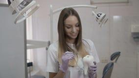 Ο οδοντίατρος με το γωνιακό έλεγχο μιμείται την επεξεργασία του δοντιού στην πλαστική μορφή απόθεμα βίντεο