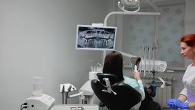 Ο οδοντίατρος ολοκληρώνει την εργασία του με έναν ασθενή Αφαιρεί τη μηχανή Bor και δίνει σε ένα κορίτσι έναν καθρέφτη για να αξιο απόθεμα βίντεο