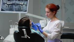 Ο οδοντίατρος ολοκληρώνει την εργασία του με έναν ασθενή Αφαιρεί τη μηχανή Bor και δίνει σε ένα κορίτσι έναν καθρέφτη για να αξιο φιλμ μικρού μήκους