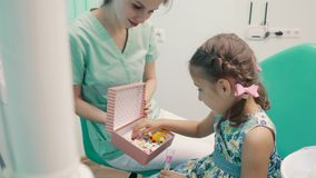 Ο οδοντίατρος παιδιών ` s διασκεδάζει το μικρό κορίτσι