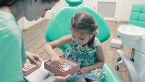 Ο οδοντίατρος παιδιών ` s διασκεδάζει το μικρό κορίτσι απόθεμα βίντεο