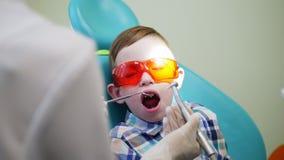 Ο οδοντίατρος παιδιών ` s μεταχειρίζεται μια συνεδρίαση αγοριών σε μια καρέκλα με το πορτοκάλι γυαλιών ασφάλειας φιλμ μικρού μήκους