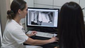 Ο οδοντίατρος παρουσιάζει στον ασθενή των ακτίνων X εικόνα του σαγονιού στην οθόνη, σε αργή κίνηση απόθεμα βίντεο