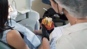 Ο οδοντίατρος παρουσιάζει στο υπομονετικό πρότυπο των δοντιών Γυναίκα στις διαβουλεύσεις στην οδοντική κλινική, σε αργή κίνηση απόθεμα βίντεο