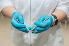 Ο οδοντίατρος, σε ένα άσπρο παλτό και μπλε γάντια κρατά στα χέρια του τα εργαλεία στοκ εικόνα με δικαίωμα ελεύθερης χρήσης