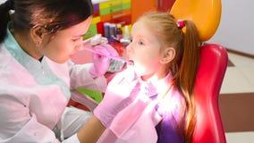 Ο οδοντίατρος των παιδιών εξετάζει τα δόντια και το στόμα ενός χαριτωμένου μικρού κοκκινομάλλους κοριτσιού σε μια κίτρινος-κόκκιν απόθεμα βίντεο