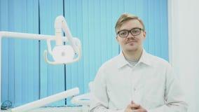 Ο οδοντίατρος φορά τα γυαλιά στο υπόβαθρο του οδοντικού εξοπλισμού μέσα Ο νέος οδοντίατρος βάζει στα γυαλιά και χαιρετά με το χαμ απόθεμα βίντεο