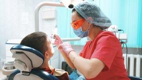 Ο οδοντίατρος φωτίζει τη σφραγίδα δοντιών photopolymer με έναν ειδικό UV λαμπτήρα απόθεμα βίντεο
