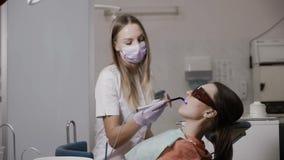 Ο οδοντίατρος χρησιμοποιεί τον οδοντικό λαμπτήρα πολυμερισμού απόθεμα βίντεο