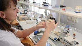 Ο οδοντικός τεχνικός εφαρμόζει την κεραμική με τη βούρτσα στα μοσχεύματα δοντιών στον εργασιακό χώρο με τα εργαλεία και τον εξοπλ φιλμ μικρού μήκους